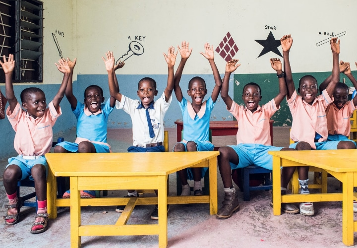 Children happily raising their hands while taking a photo